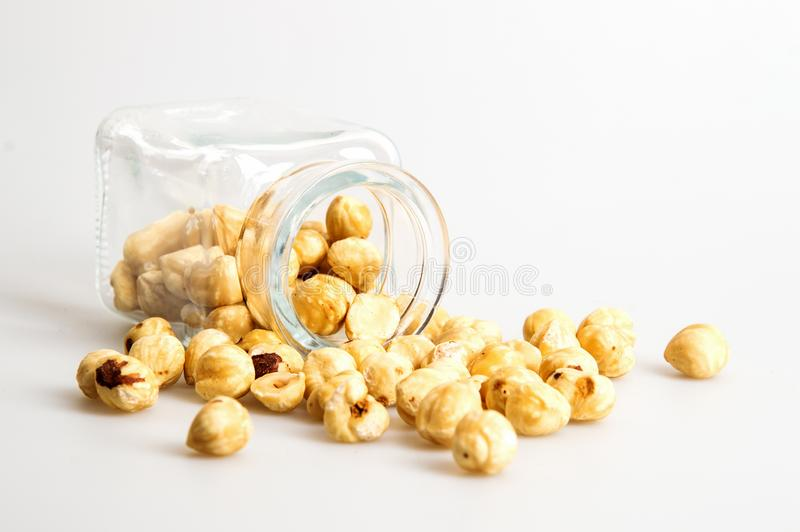 Close up. A glass jar is lying sideways, a bunch of hazelnuts are scattered around it. White background. Copy space royalty free stock photos