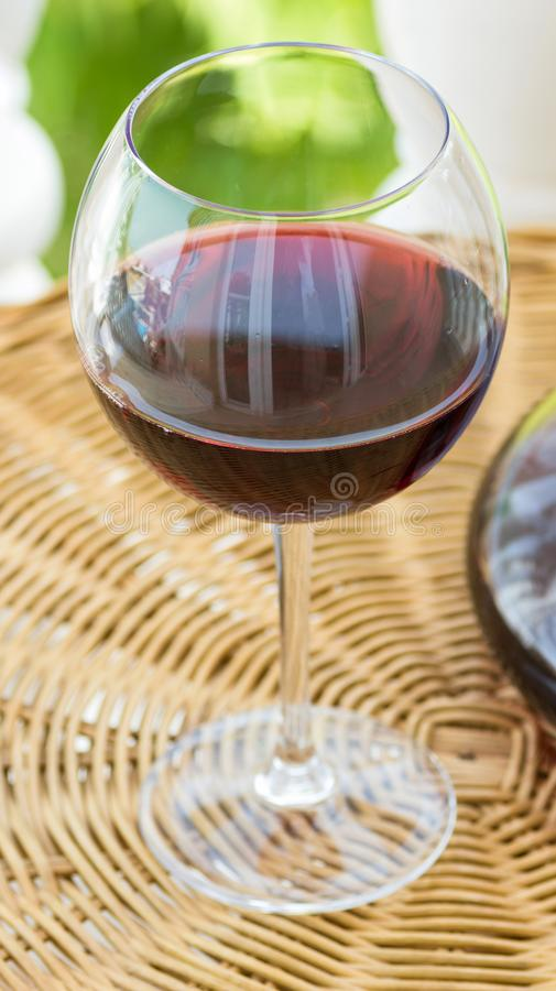 Close Up of Glass of Red Wine and Decanter on Rattan Wicker Table in Garden Terrace of Villa or Mansion. Authentic Lifestyle Image. Relaxation Indulgence royalty free stock photo
