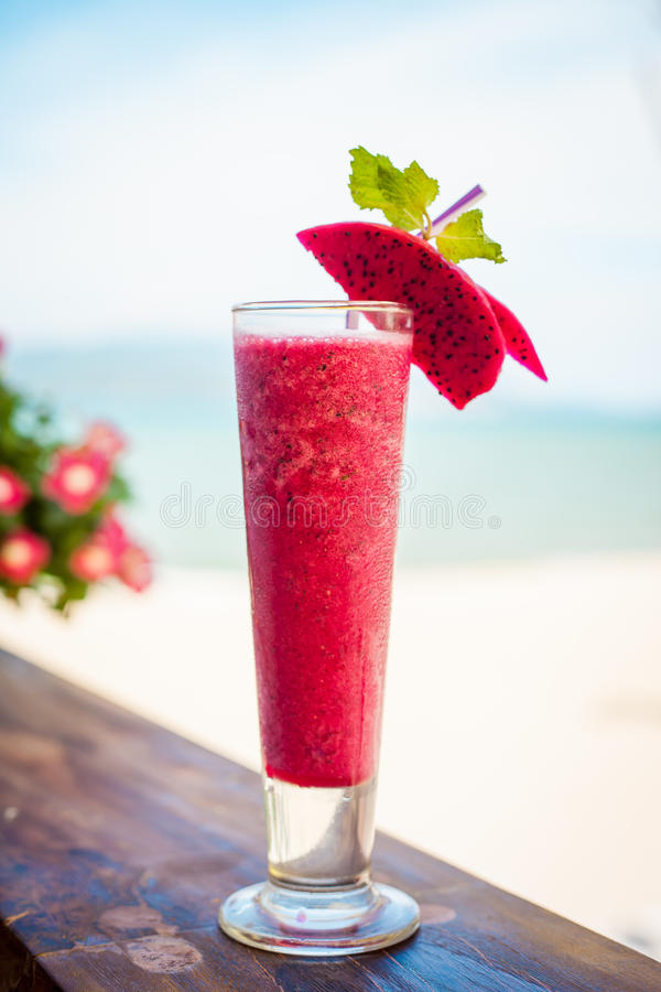 Close up of glass with refreshing orange cocktail with dragon fruit on beach. stock photos