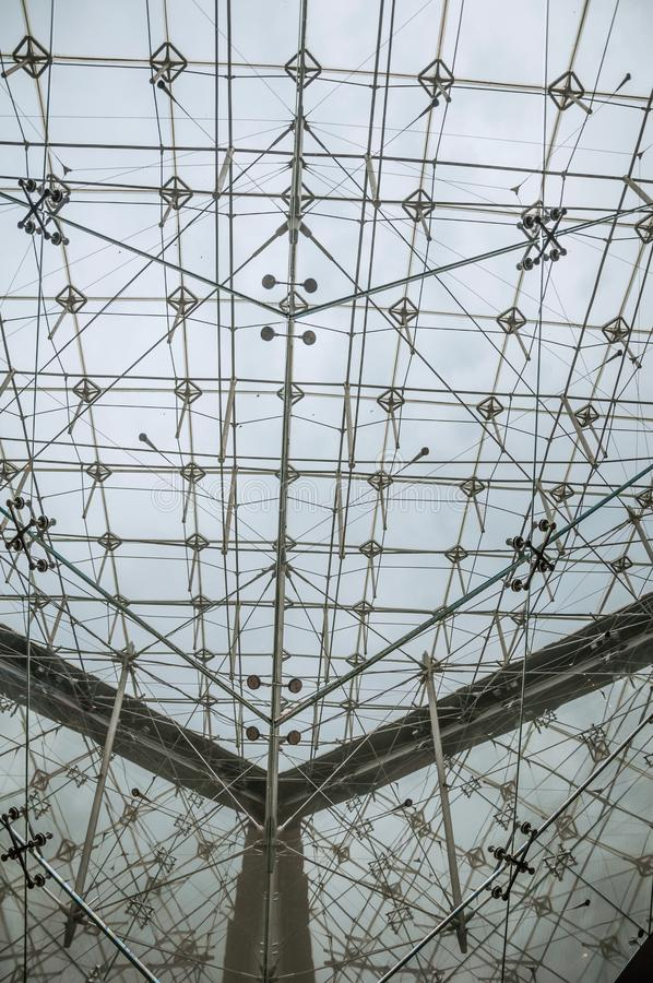 Close-up of the glass and steel ceiling structure on the Louvre Museum in a cloudy day at Paris. stock image