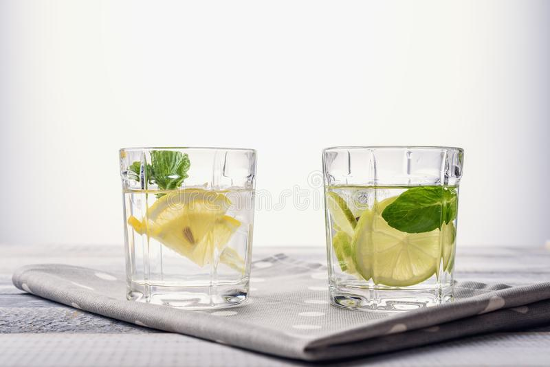 Close-up glass of water with lemon, lime and mint on light gray wooden background. Detox concept royalty free stock image