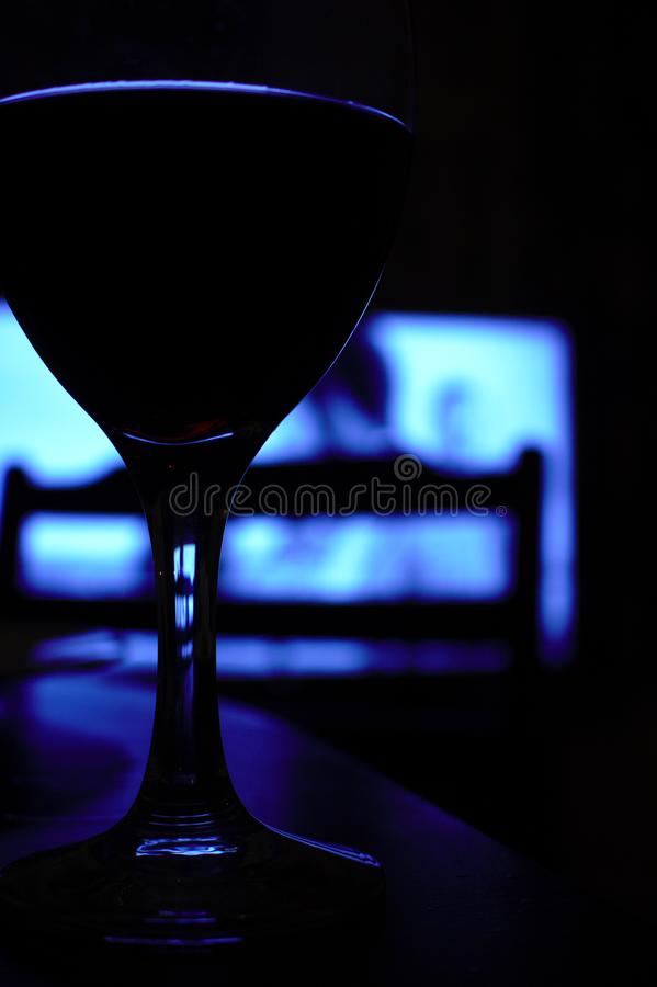 Close up of a glass of wine sitting on a table, in the dark stock photography