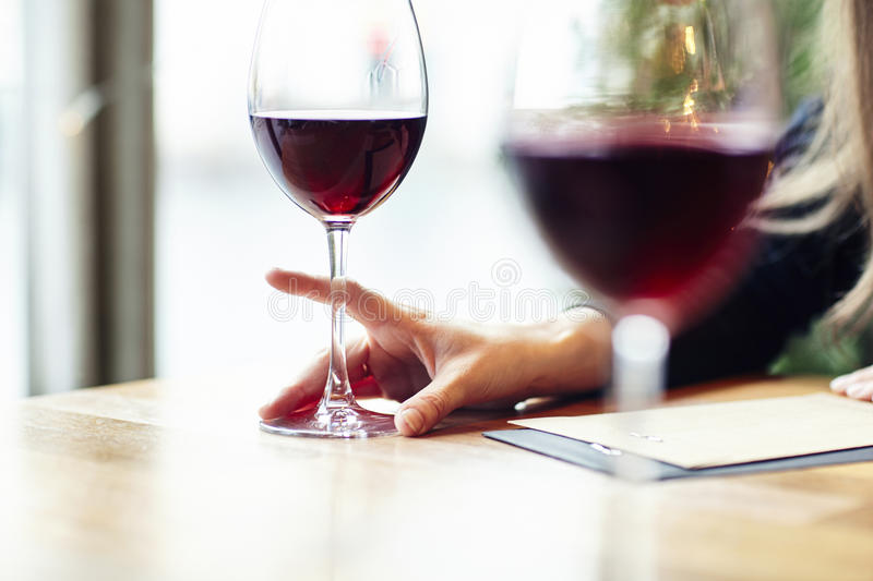 Close-up of glasses of red wine in a cafe. Friends meeting indoor. Hipster paper envelope royalty free stock images
