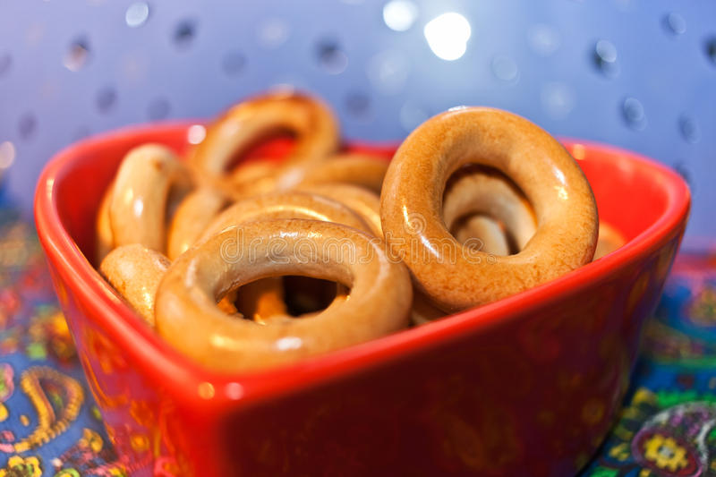 Close-up glazed bagels on red plate in shape of heart. Selective stock photo