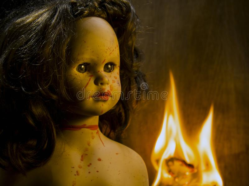 Close-up of a gloomy bloodied doll illuminated by warm light. Against a fire stock photo