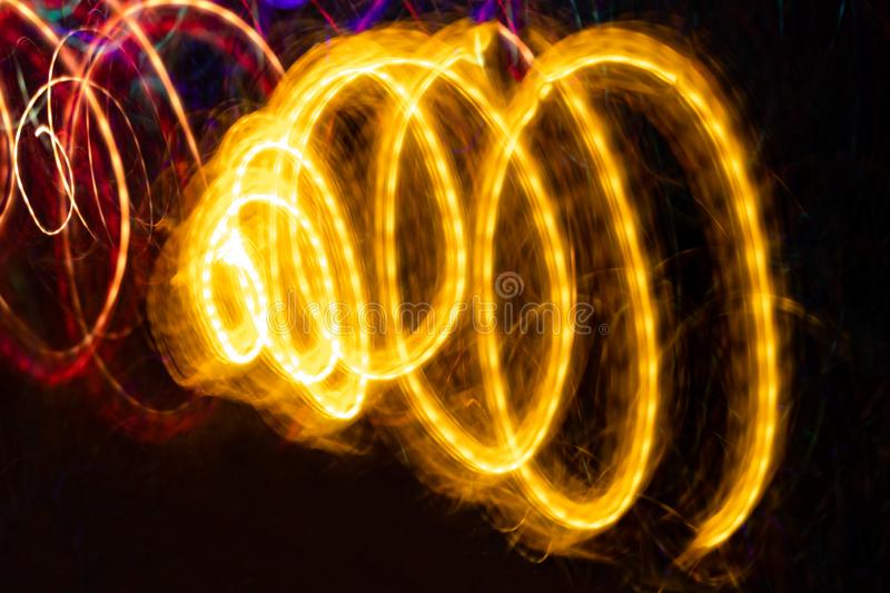 Close-up glowing yellow spiral on black background. Abstract drawing. Photographic effect with long exposure stock images
