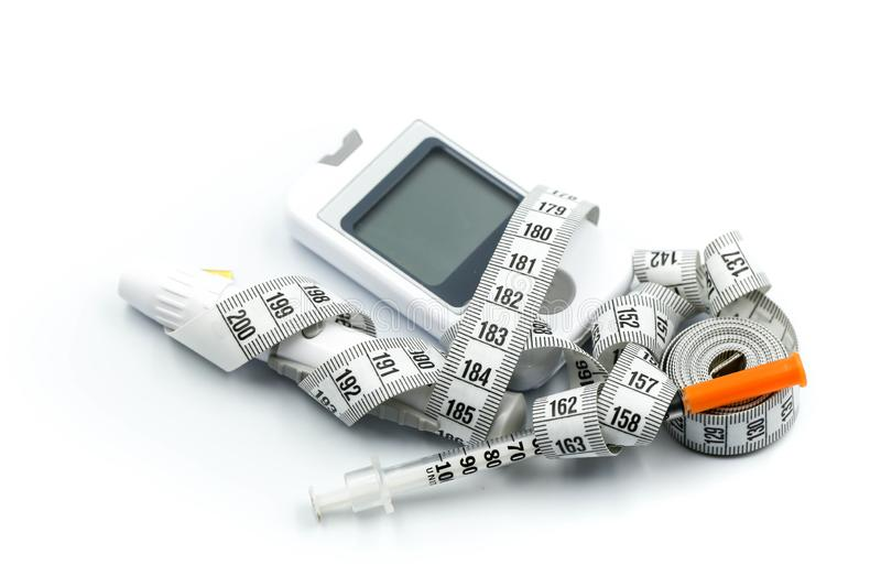 Close up of glucometer with blood sugar test stripe, insulin injection syringes and pills with Measure stock photography