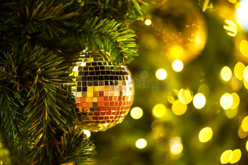 Close Up gold balls of Christmas tree decorations on abstract light golden bokeh background. royalty free stock image