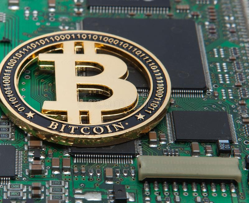 Close-up of gold bit coin, computer circuit board with bitcoin processor and microchips. Electronic currency, internet finance ryp stock photo