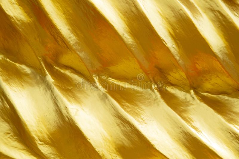 Golden Yellow Texture Background. Close-up of gold leaf gilt detail on a buddha statue in Wat Phra Yai located on Pratumnak Hill in Pattaya, Chonburi, Thailand stock image