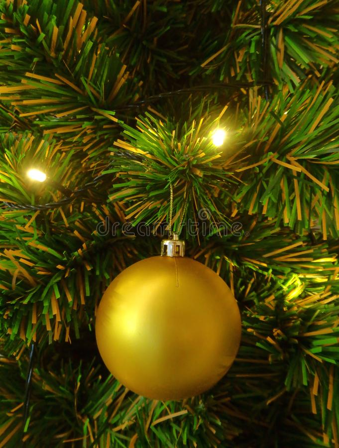Close-up of a Gold Shiny Ball Ornament on the Christmas Tree, Vertical Photo stock image