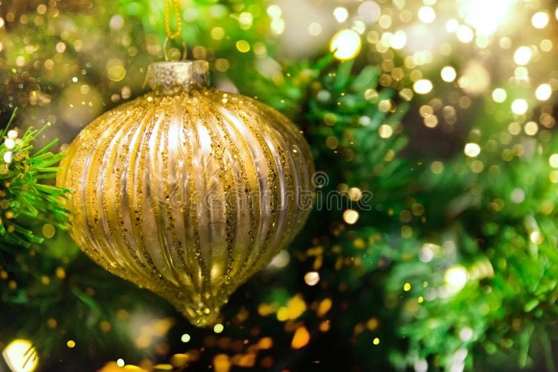 Close up of golden ball ornament hanging on decorated Christmas tree. Sparkling garland bokeh lights glitter. Magic cozy holiday stock image