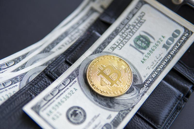 Close up golden coin bitcoin on us hundred dollars on leather a wallet with full of money. Profit from mining crypto stock photo