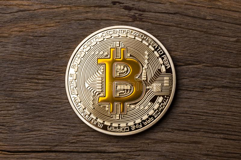 Close up of golden cryptocurrency yellow bitcoin on wooden backg royalty free stock images