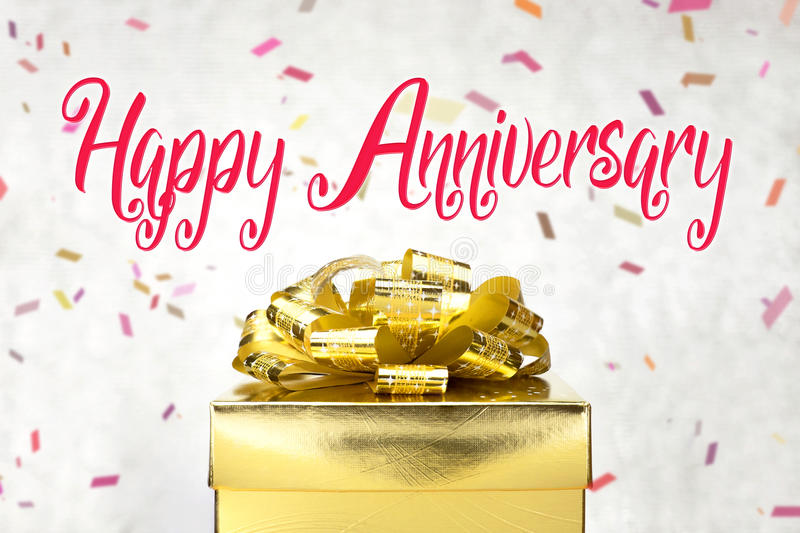 Close up Golden present box with Happy Anniversary word and confetti blur background royalty free stock images