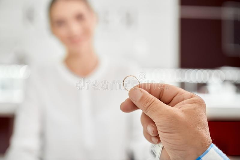 Close up of golden wedding ring that holding man`s hand stock photography