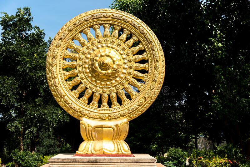 Close up Golden Wheel of Dhamma or Wheel of life and symbol teaching of the Lord Buddha, Symbol of Buddhism in the temple,. Backdrop tree stock image