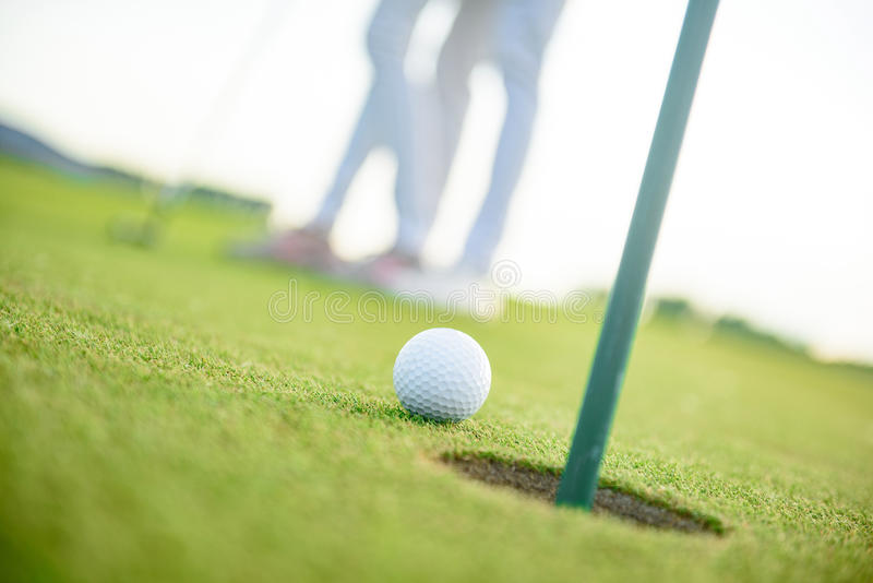 Close up of golf ball next to hole stock images