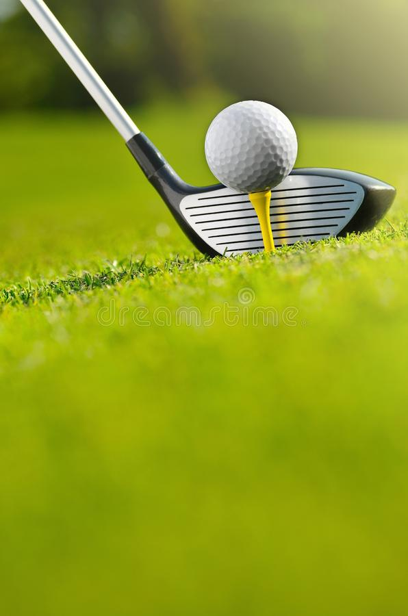 Let`s golf today. Close up of a golf ball on the tee and the iron royalty free stock photo