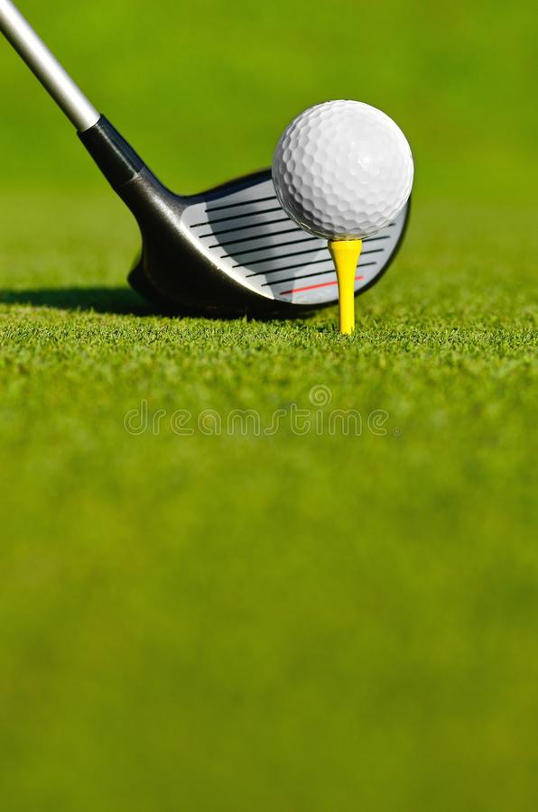 Let`s golf today!. Close up of a golf ball on a yellow tee stock image