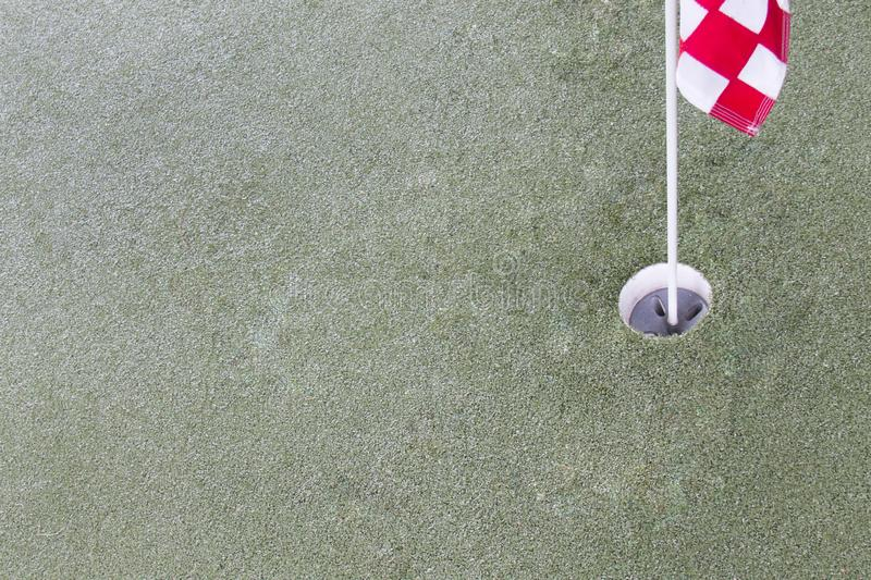 Close up of golf driving range. Hole and red flag on green grass royalty free stock photo