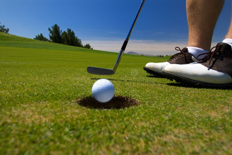 Close up of golfer teeing off. An up close image of a golfer preparing to tee off royalty free stock image