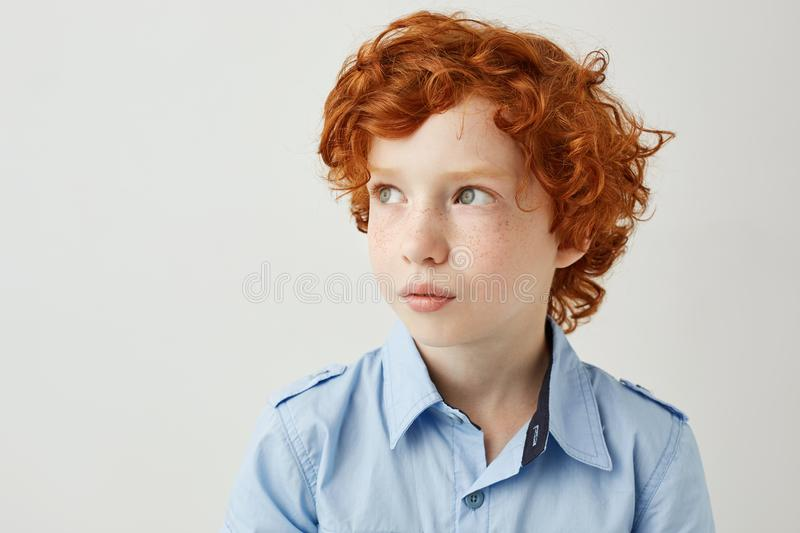 Close up of good-looking little boy with red curly hair and freckles looking aside with interested and relaxed stock image