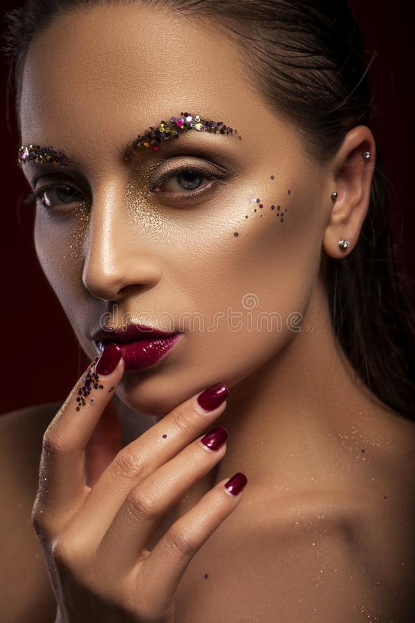 Close up of a gorgeous a bit brutal woman with creative fashion make up: glitters and glamour shine. look stock photos