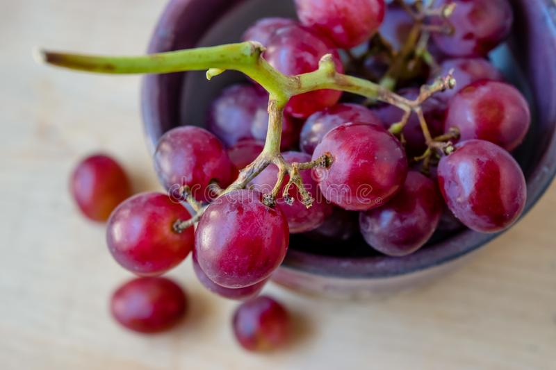 Fresh grapes in bowl on wooden table stock photo