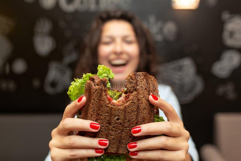 Close-up grappig vaag protrait van jonge vrouwengreep gebeten sandwich door haar twee handen Sandwich in nadruk Donkere achtergro royalty-vrije stock fotografie