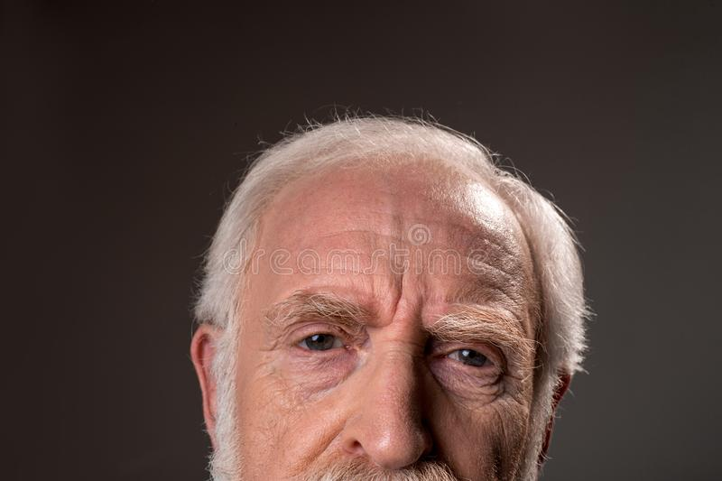 Negative senior man looking exhausted. Close up of gray haired male half face wrinkling his forehead, expressing tiredness. on grey background stock photos