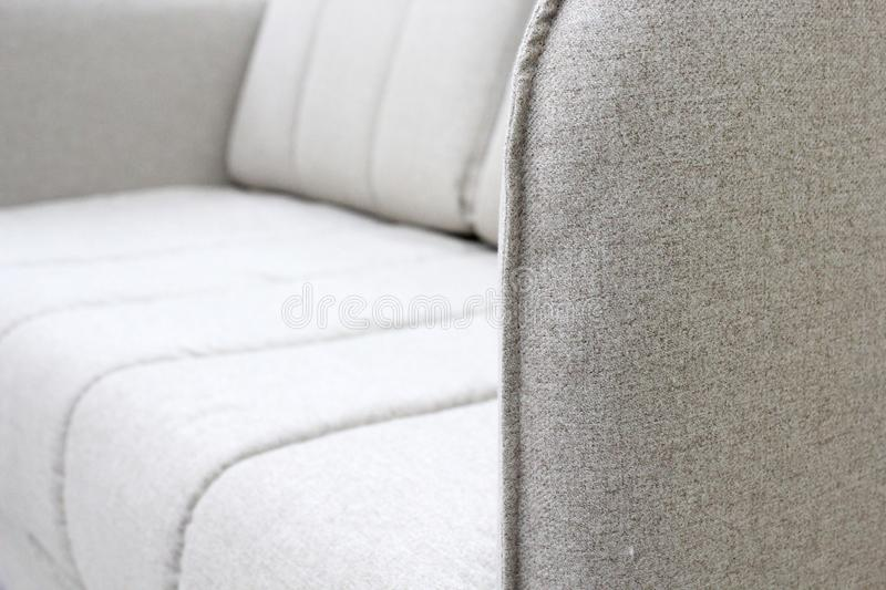 Close-up of gray sofa with armrest. Textiles, new furniture modern design. With free space for text. stock image