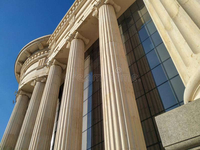 Close up of Greek style pillars and columns old fashioned style historical white architecture building with modern glass windows royalty free stock images
