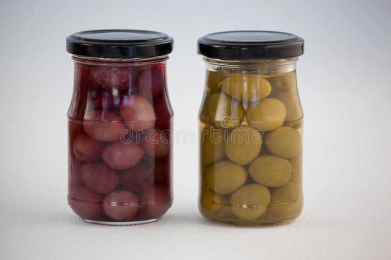 Close up of green and brown olives in jar royalty free stock image