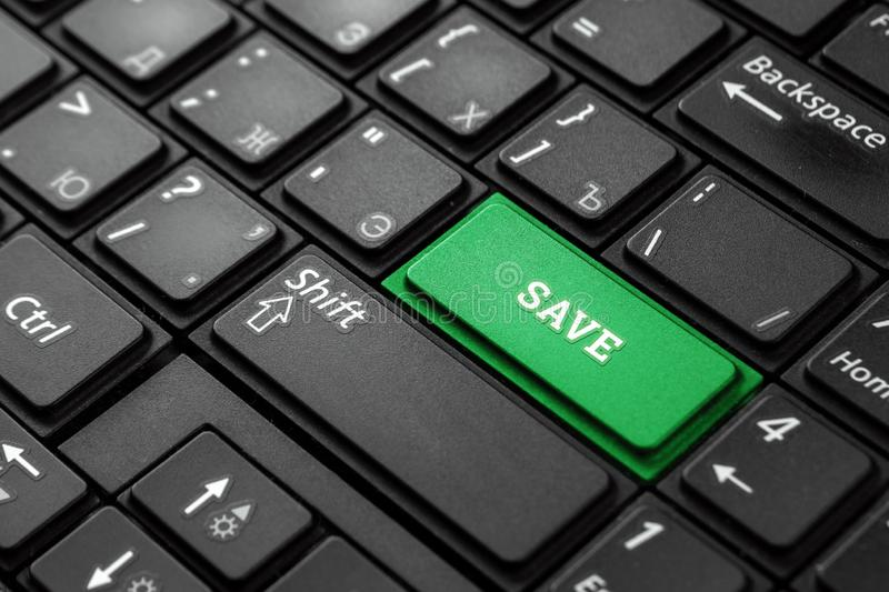 Close up green button with the word save, on black keyboard. Creative background, copy space. Concept magic button stock photography