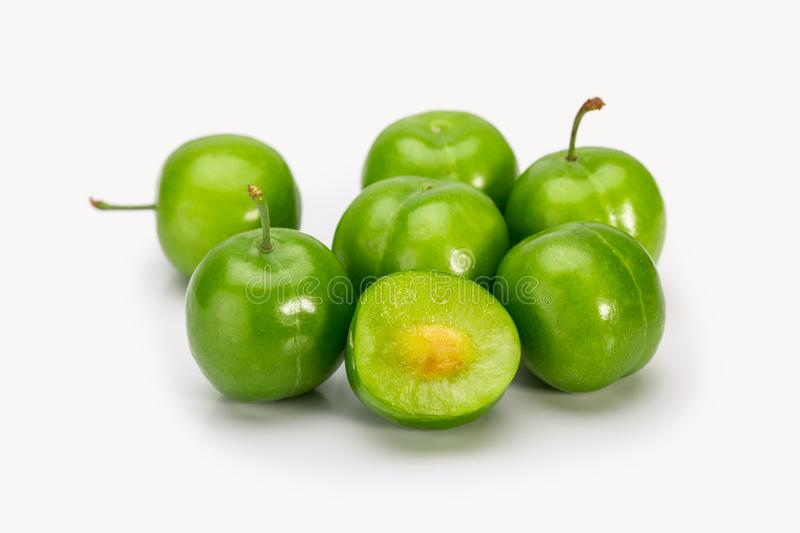 Close Up Of Green Plums Or Greengage showing the flesh and the s. Eed of the fruit Isolated On White Background, Popular Spring Fruits With A Very Sharp Sour stock photo
