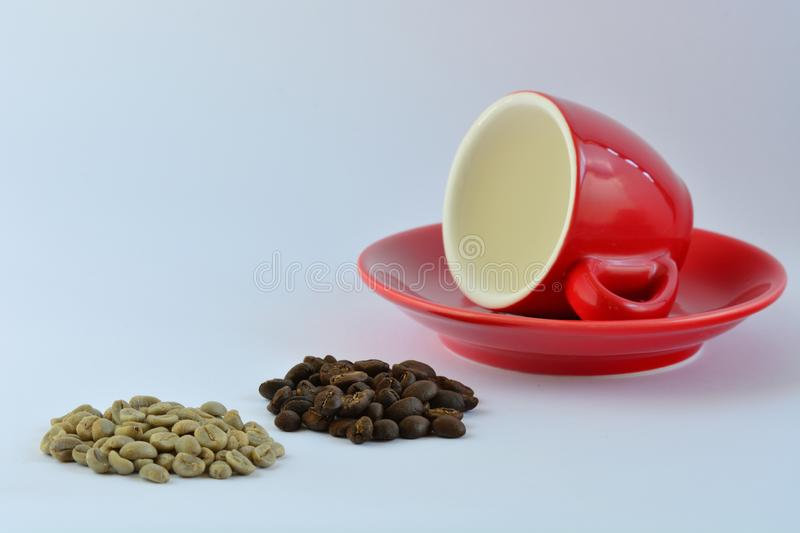 A close-up photo of a bright red espresso coffee cup, some green coffee beans and some roasted coffee beans on white background. Close-up; green and roasted royalty free stock photography
