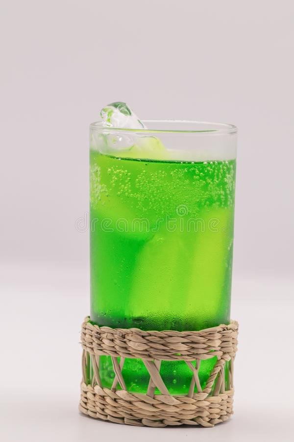 Close up green soft drink  with in wickerwork saucer from dry sedge on white. Soft drink in isolate white background stock images