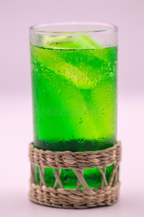 Close up green soft drink  with in wickerwork saucer from dry sedge on white. Soft drink in isolate white background stock photo