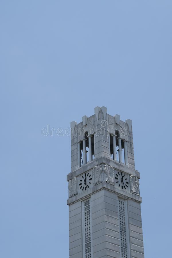 Close up grey Bell and clock tower up against blue clear sky. stock photos