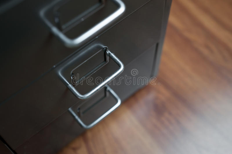 Close up of grey drawer. Close up of grey drawer with stainless handle on wooden floor royalty free stock photography