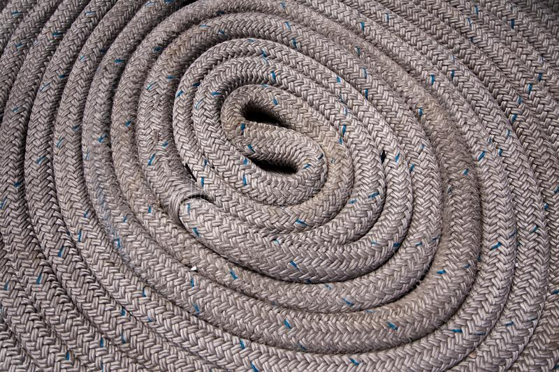 Close up of grey nautical rope coiled and with blue highlights royalty free stock photography