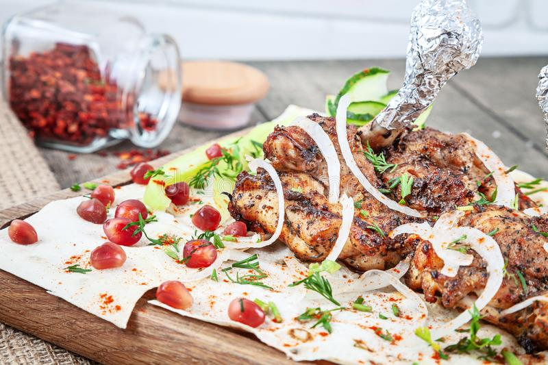 Close up grilled chicken, chicken skewers, pierzola served on pita bread with onion and herbs, spices. eastern shashlik or kebab stock images