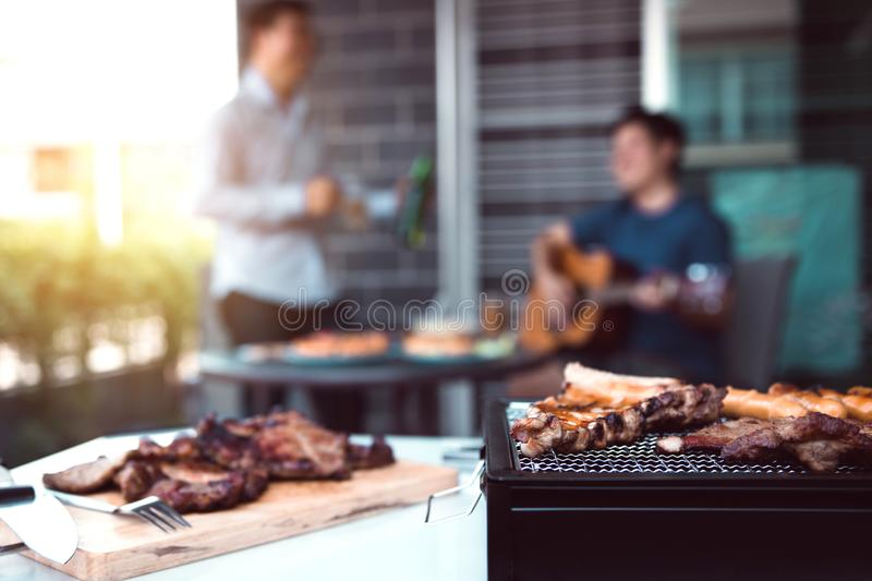 Close up grilled meats and various food on the grill and celebrations of friends who are playing guitar and sing together in their stock photography