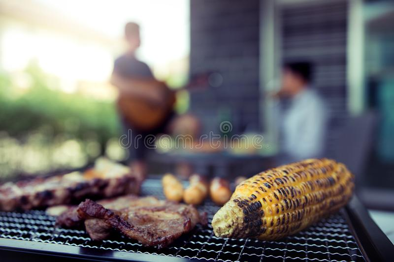 Close up grilled meats and various food on the grill and celebrations of friends who are playing guitar and sing together in their stock photo