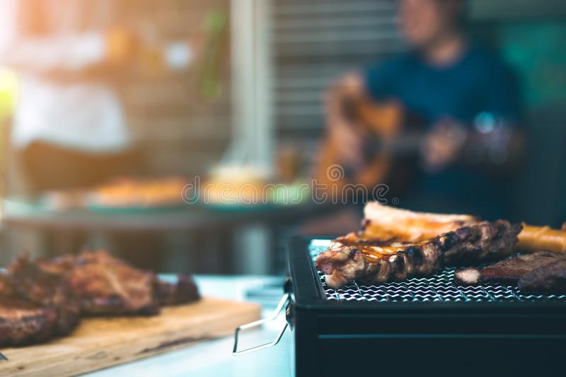 Close up grilled meats and various food on the grill and celebrations of friends who are playing guitar and sing together in their stock photos