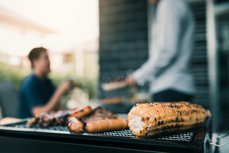 Close up grilled meats and various food on the grill and celebrations of friends who are playing guitar and sing together in their stock images