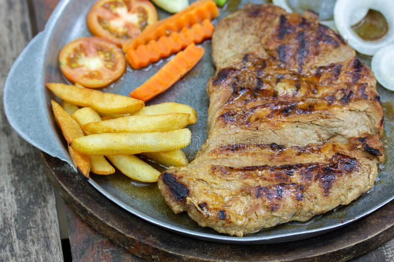 Close up of Grilled Pork Steaks and French Fries with Vegetable stock photos