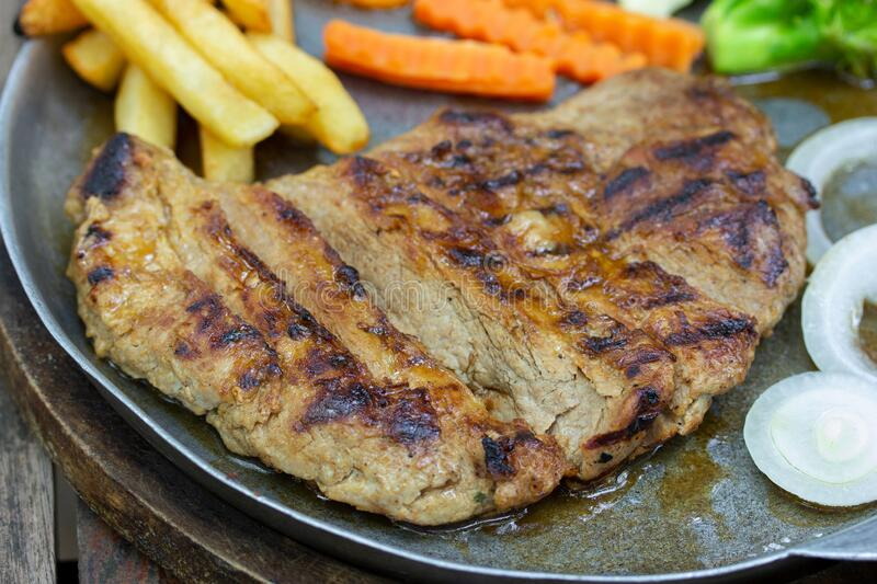 Close up of Grilled Pork Steaks and French Fries with Vegetable royalty free stock images