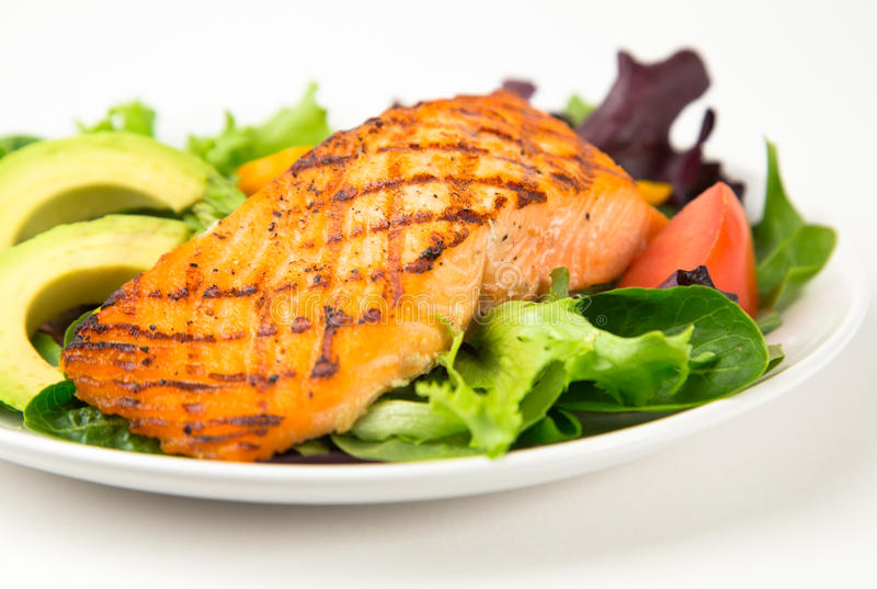 Grilled Salmon. Close up of a Grilled Salmon salad with mixed greens, tomatoes and avocado. Shallow depth of field stock photos